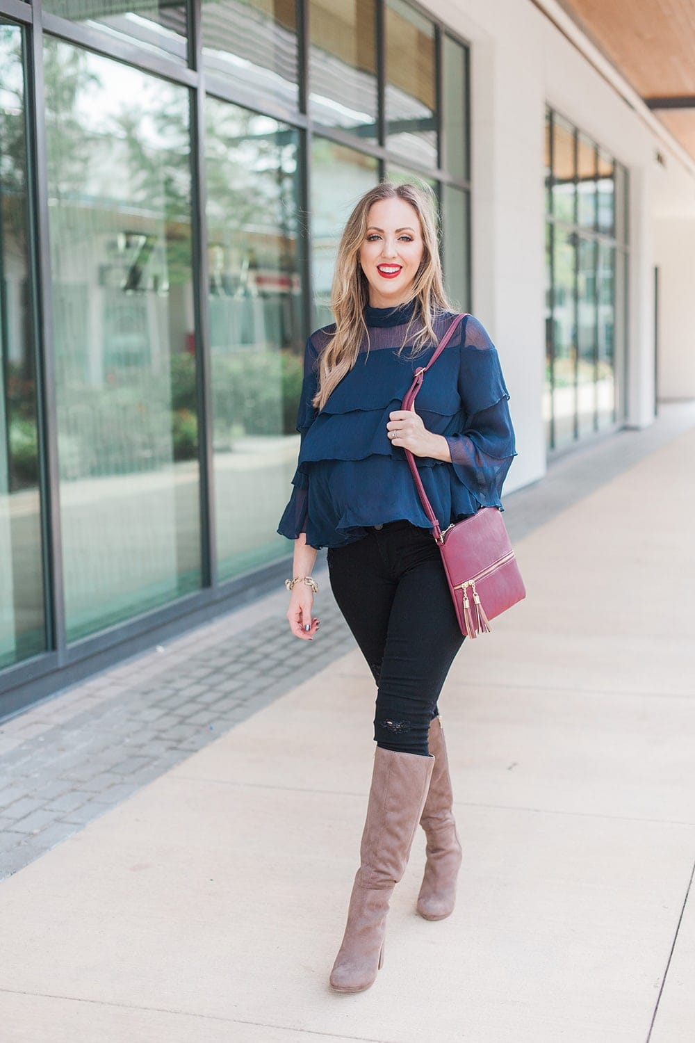 gorgeous fall or holiday outfit idea - ruffle blouse with distressed denim and tall boots