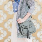 floral cami, pleated skirt, long cardigan, and saddle bag