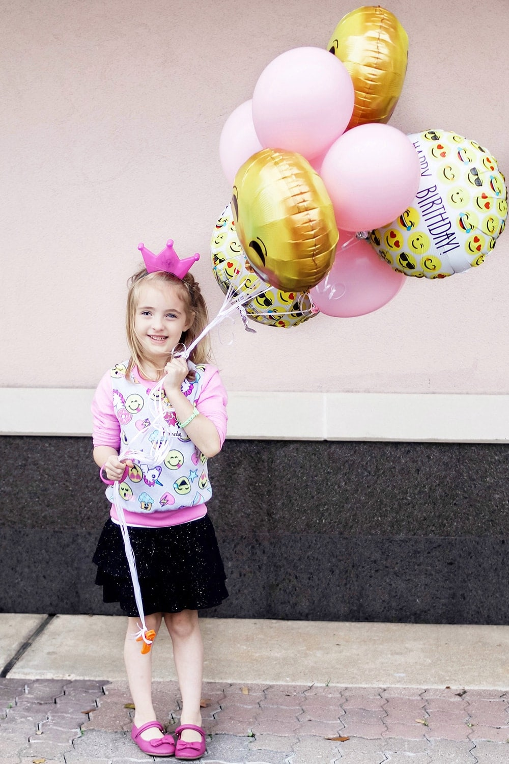 birthday girl holding pink and emoji balloons