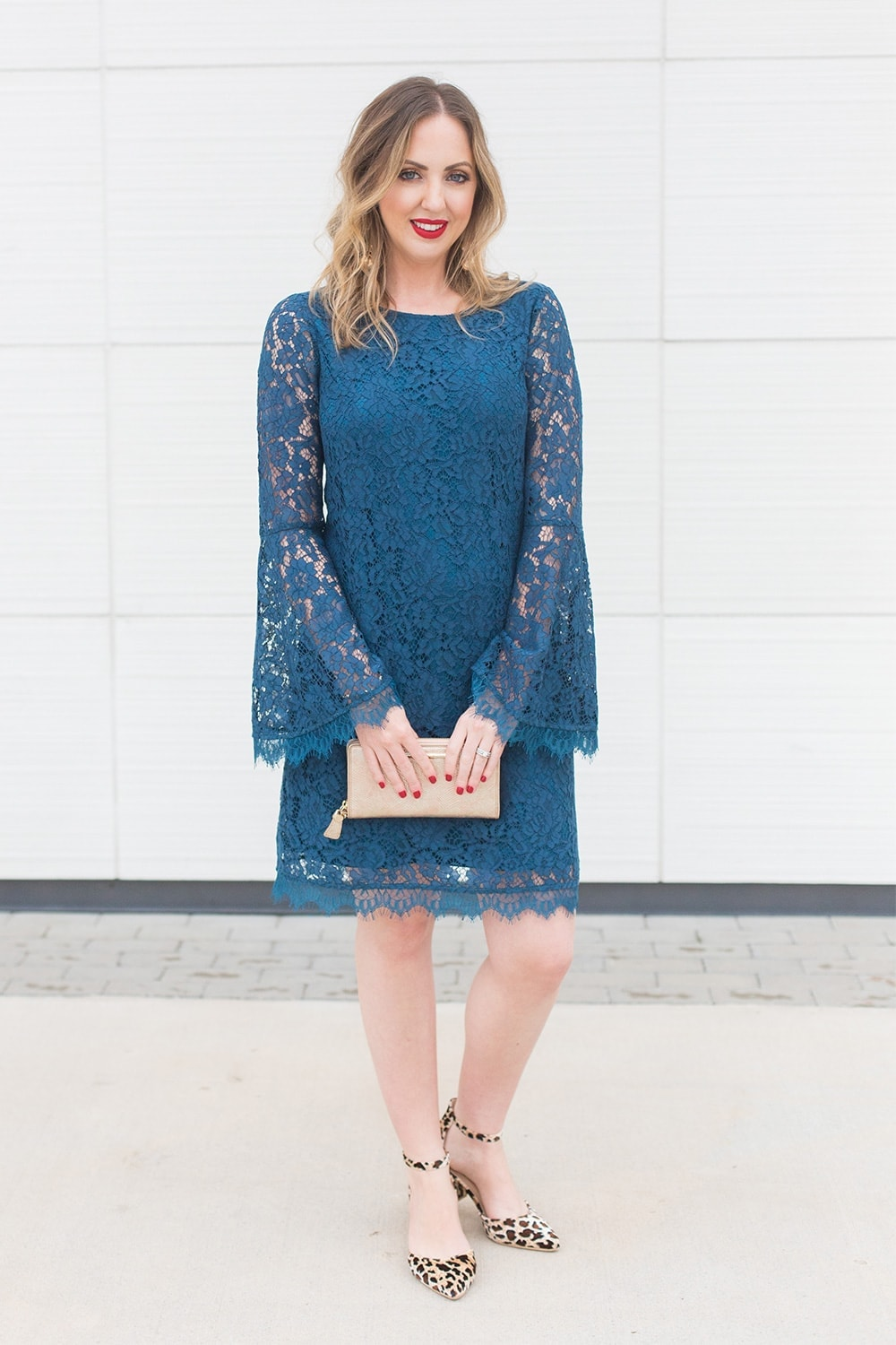 Houston blogger Meg O. on the Go wearing a blue lace bell sleeve dress with leopard print shoes, gold earrings, and a gold clutch