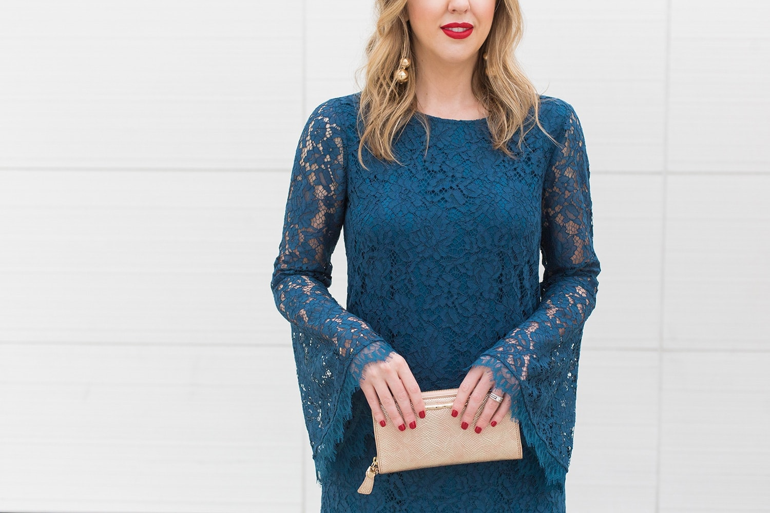 detail shot of blue bell sleeve lace dress with gold clutch, gold earrings, and red lipstick - by Houston blogger Meg O.