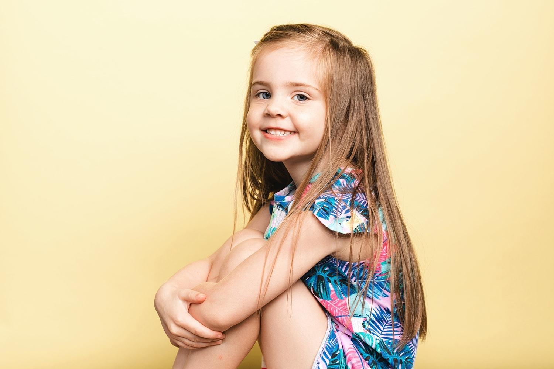 Child headshot with yellow background